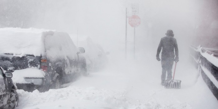Pedestrians brave the storm as it intensifies. | Image source: Huffington Post